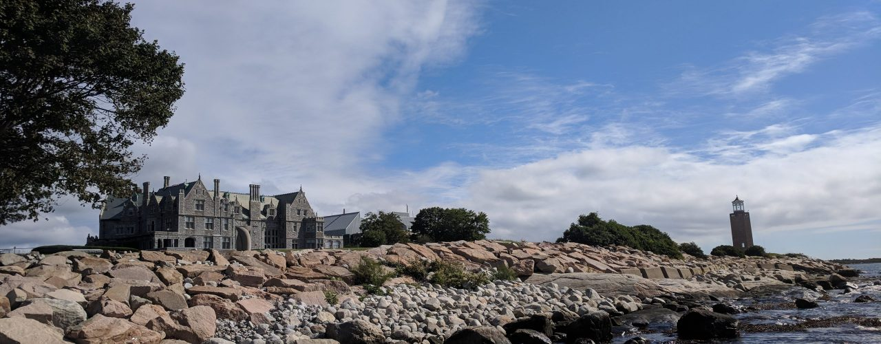 A rocky coastline extends up with a stone mansion in the center background, a lighthouse to the right, and part of a tree to the left