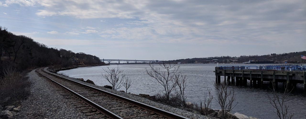 Train tracks run down the coastline towards a large bridge in the far distance. There is a dock on the right.